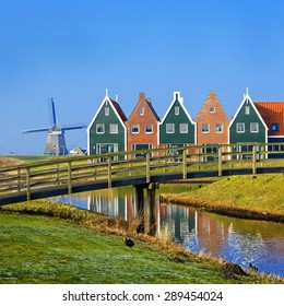 Colored houses of marine  park in Volendam reflected in the water on a winter morning, Netherlands