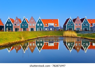 Colored houses of marine  park in Volendam reflected in the water, Netherlands