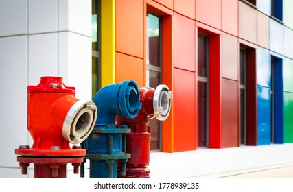 Colored hydrants with colored building in background, hydrants and multi-colored building, close up of three colored hydrants