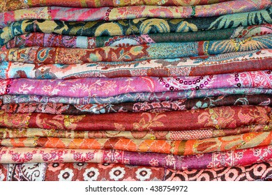 Colored Indian cashmere shawls are composed of a stack background