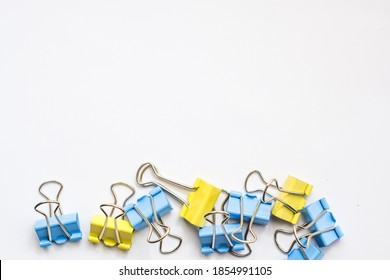 Colored iron paper clips. paper clips with many unique pastel color variants isolated on a white background, Binder clip is a simple device for binding sheets of paper together, metal clips in chaos