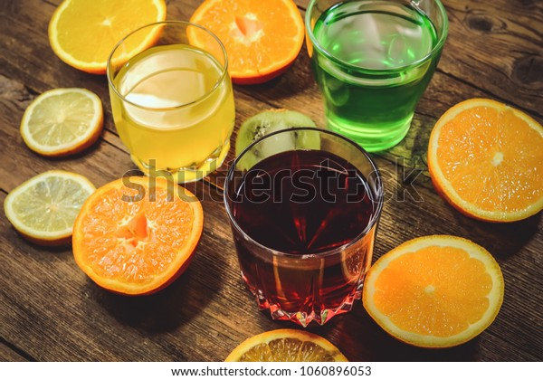 colored juices in glass jars. with slices of citrus on a wooden background.