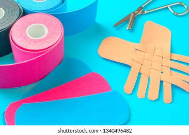 colored kinesio tapes with a pair of scissors