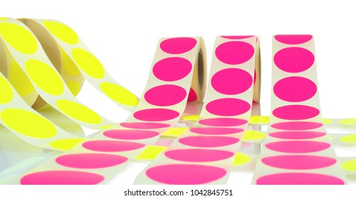 Colored label rolls isolated on white background with shadow reflection. Color reels of labels for printers. Labels for direct thermal or thermal transfer printing. Yellow and pink labels background.