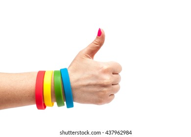 Colored latex bracelet on the arm with thumbs up on White Background. Multicolor