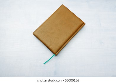 Colored leather diary book laying on wooden table