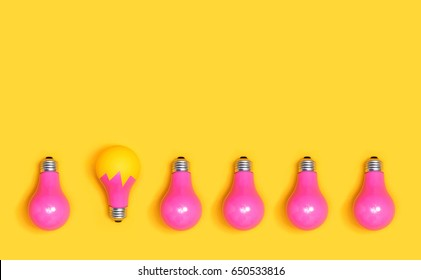 Colored light bulbs aligned on a yellow background