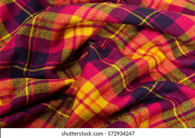 Colored lines and square pattern. Scottish checked fabric crumpled.