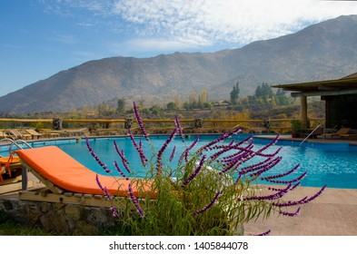 colored loungers by the pool. pool against the backdrop of the mountains. orange sun loungers. white towels