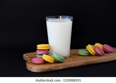 Colored macaroons with milk in a glass