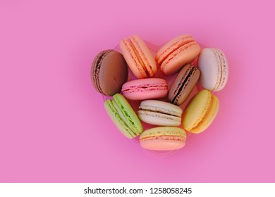 colored macaroons on a pink background, heart of macaroon