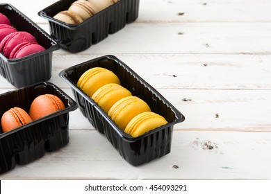 Colored macaroons on white wooden background