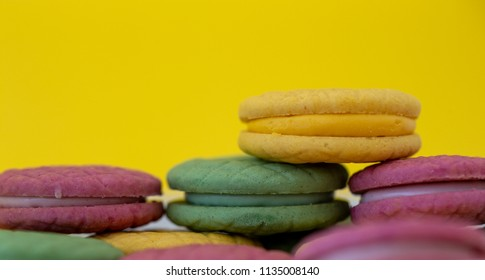 Colored macaroons on yellow background