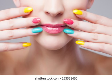 Colored manicure, Woman face with rainbow makeup and manicure