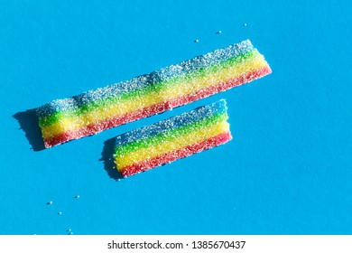 Colored marmalade in the sugar on the blue background. Natural rainbow colored marmalade candy. Copy space, empty template for text