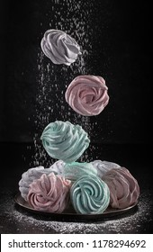 Colored Marshmallow or Zephyr   flying in freeze motion,  in powdered sugar. Concept of flying food. Homemade sweets