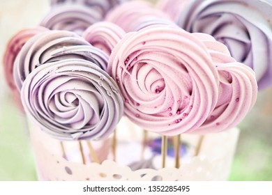 Colored meringue on stick, in vase on buffet outdoor. Pink and violet colors.