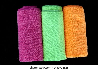colored microfiber cleaning cloths, orange, pink, green colored microfiber cloths black back ground,