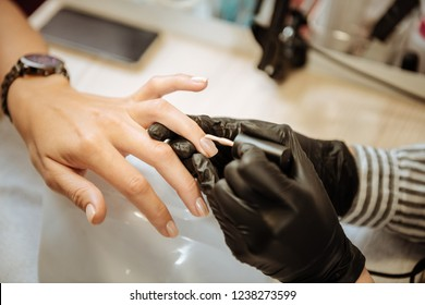 Colored nails. Beautiful stylish woman wearing had watch having her nails colored visiting beauty saloon