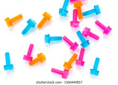 Colored neon translucent plastic toy bolts on white background. Flat lay. Concept World Dad's Day, unisex toys for early development, role-playing games. Layout for social media, toy stores