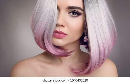 Colored Ombre bob hair extensions. Beauty Blonde Model Girl with short pink hairstyle isolated on gray background. Closeup woman portrait.