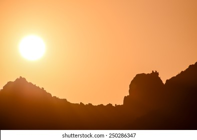 Colored Orange Sun Setting Behind the Mountains
