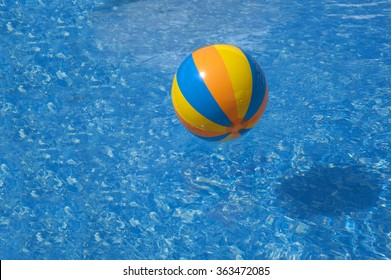 Colored orange yellow blue inflatable ball floats at pool with blue white marble background