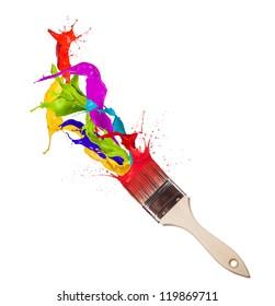 Colored paint splashes splashing from paintbrush on white background