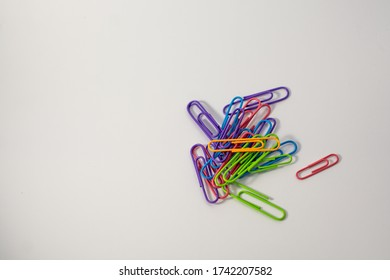 Colored paper clips lie together. Around white background. Blue, yellow, purple, green, pink and orange. Plastic paper clips for documents. Office and educational equipment. Tools for paper work.