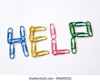 Colored paper clips spelling the word help on white background