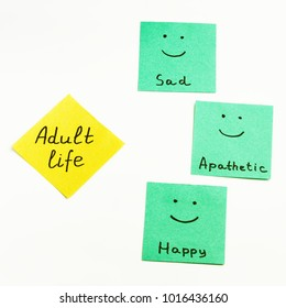"""Colored paper notes with inscriptions """"Adult life"""", """"Happy"""", """"Sad"""", """"Apathetic"""" on white bacground."""