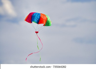 Colored paper parachute and frills floating in the air checking the winds