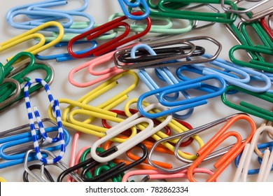 Colored paperclips scattered across a white background