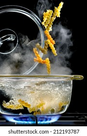 colored pasta falling in a glass saucepan on gas stove