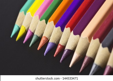 colored pencils aligned in a row, a full color pallete, against black