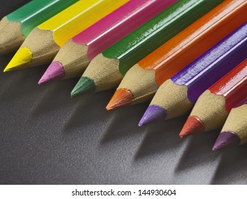 colored pencils aligned in a row, a full color palette, against dark background