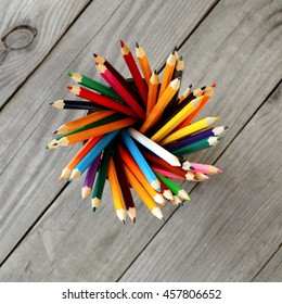 Colored pencils background. Set of colored pencils in the holder on wooden background, top view