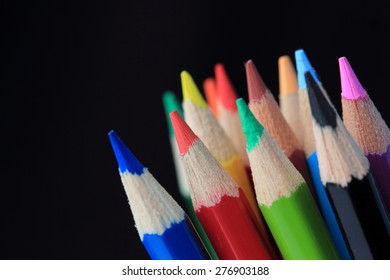 Colored pencils in the black background,White ,shallow depth of field