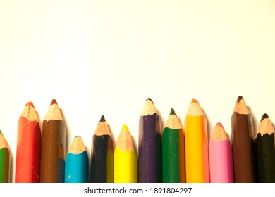 Colored pencils at the bottom of the frame. White background.
