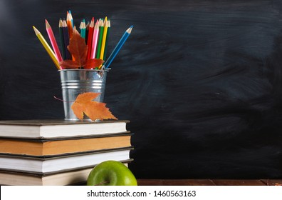 Colored pencils and fall leaves on stack of books. Green apple on wooden desk.  Classroom blackboard with copy space in background. Education, September, back to school concept - Shutterstock ID 1460563163