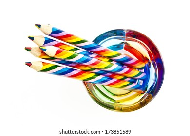 Colored pencils in a colored glass isolated on white background