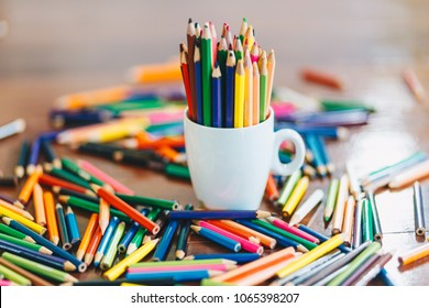 colored pencils in a glass on wooden background