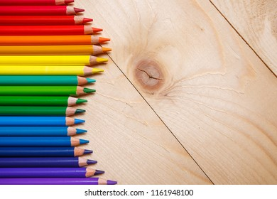 Colored pencils are laid out on the left side of the background. On a wooden background. Top view, flat lay. copyspace