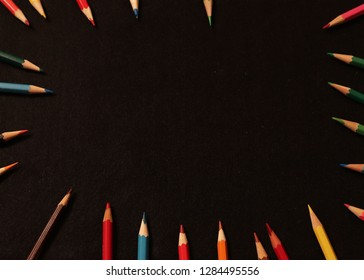 colored pencils lie in a circle on a dark background