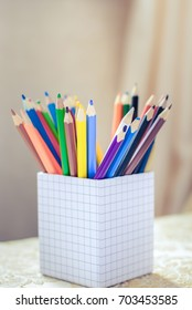 A lot of colored pencils in a light box in a light room