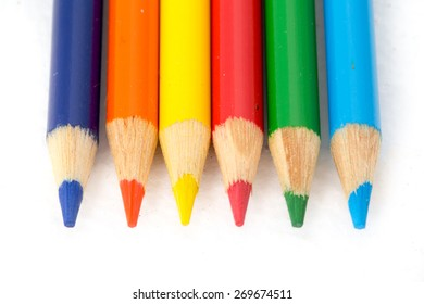 Colored pencils lined up on white.  They match the rainbow colors in order.