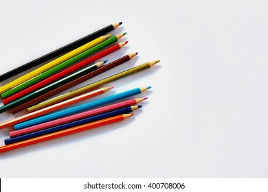 Colored pencils lying on the white paper