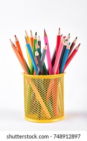 Colored pencils in metal holder. Multicolored pencils in yellow shaped metal basket isolated on white background.