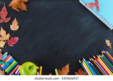 Colored pencils, notebook, crayons, green apple and fall leaves on blackboard. Top view, copy space, clack, frame, border. Education, autumn, back to school concept