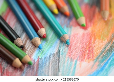Colored pencils on an abstract background. Close-up.